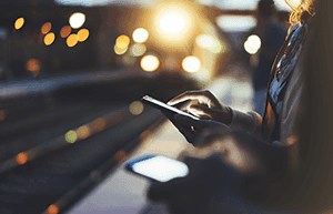 Woman using smartphone at night with lights of approaching train